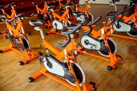 Rows of exercise bikes in modern sports hall are waiting for people to working out