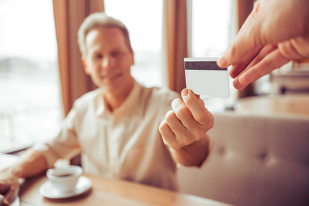 business for the middle: Handsome middle aged businessman is paying with a credit card for business lunch at the restaurant, close-up