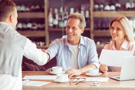 Business-Leute arbeiten während Business-Lunch. Frau hält ein Dokument, zwei Männer sind Händeschütteln