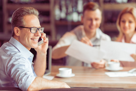 mobile communication: Handsome middle aged businessman in eyeglasses is talking on the mobile phone, in the background young business man and woman working at the restaurant