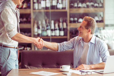 Handshake of two handsome businessmen in casual clothes meeting for working at the restaurant