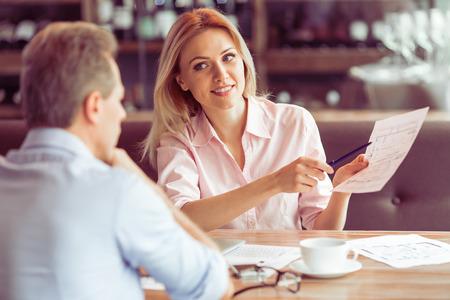 美しいビジネス女性レストラン ビジネスの会議中に男にドキュメントと説明するビジネスの事件を保持しています。