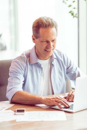 banking concept: Handsome middle aged businessman in casual clothes is using a laptop and smiling while working