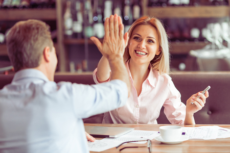 two people meeting: Beautiful business woman is giving high five and smiling to man during business meeting at the restaurant Stock Photo
