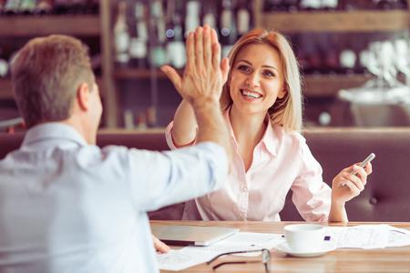 Prachtige zakelijke vrouw is het geven van hoge vijf en glimlachen naar de mens tijdens zakelijke bijeenkomst in het restaurant