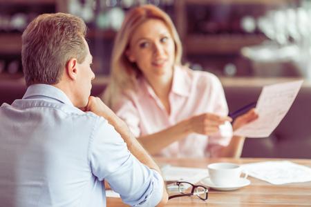 아름 다운 비즈니스 여자 문서를 들고와 레스토랑에서 비즈니스 회의 남자 비즈니스 일을 설명한다
