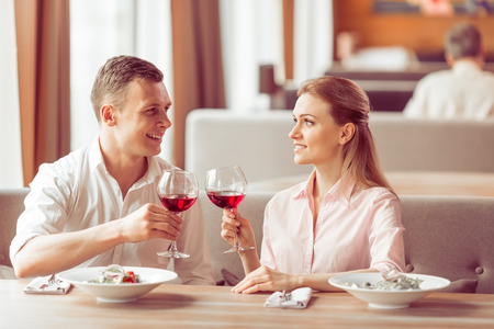 Schöne junge Paar trinkt Wein, sprechen und lächeln beim Mittagessen im Restaurant photo