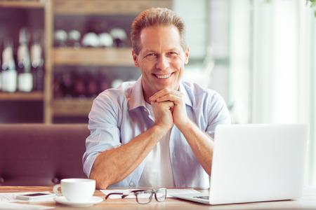 Apuesto hombre de negocios de mediana edad en ropa casual está utilizando una computadora portátil y sonriendo mientras trabajaba en el restaurante