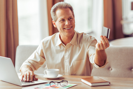 business for the middle: Handsome middle aged businessman is paying with a credit card for business lunch at the restaurant Stock Photo