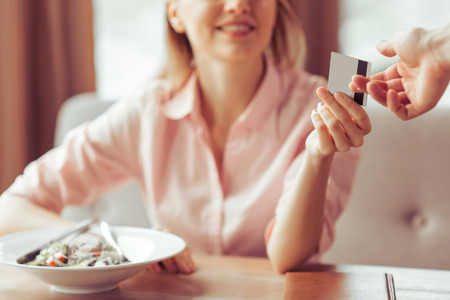 Schöne junge Business-Frau ist im Restaurant mit einer Kreditkarte für Business-Lunch bezahlen, close-up photo
