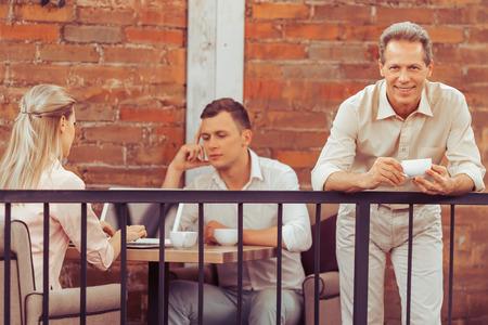 Stattlicher Geschäftsmann mit einer Tasse Kaffee, im Hintergrund ein Mann und eine Frau mit einem Laptop, während auf dem Balkon des Restaurants arbeiten photo