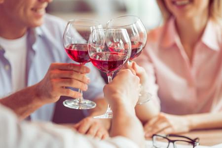 Geschäftsleute, die lächeln, reden und klirrende Gläser Wein zusammen während Business-Lunch, close-up photo