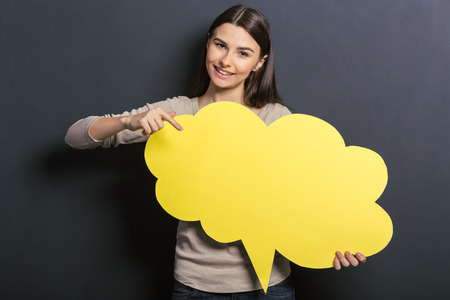 solve problem: Beautiful young female student is holding a yellow speech bubble, pointing on it and smiling, standing against blackboard