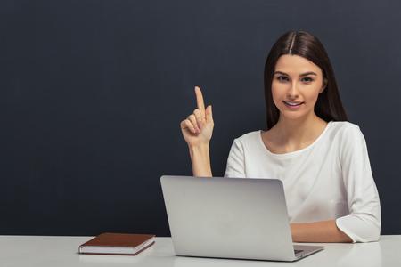 白いブラウスで美しい学生は指を追い、黒板とノート パソコンとテーブルに座ってカメラ目線