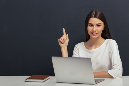 Beautiful student in white blouse is keeping finger up and looking at camera, sitting at a table with a laptop against blackboard Stock Photo