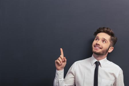 beau jeune homme: jeune étudiant Beau en chemise blanche classique est souriant, à la recherche et pointant vers le haut, debout contre tableau noir Banque d'images