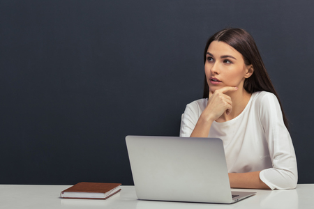 thinking woman: Thoughtful beautiful student in white blouse is keeping hand on chin and thinking, sitting at a table with a laptop against blackboard
