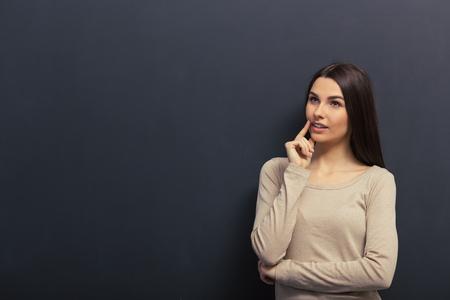 思いやりのある少女が離れている、あごに手を維持する笑顔と考えて、黒板に立っています。 写真素材