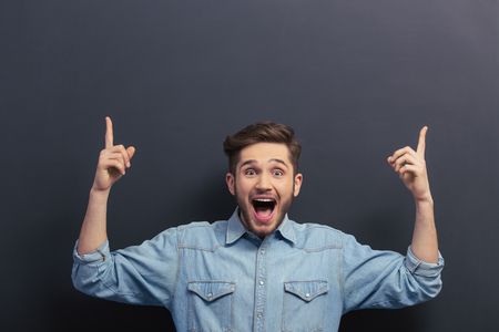 Handsome young student in jeans shirt is pointing up, looking at camera, shouting and smiling, standing against blackboard