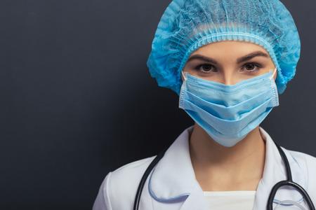 nurse cap: Hermosa joven médico en blanco médica bata, gorro y mascarilla está mirando la cámara, de pie contra la pizarra, primer plano