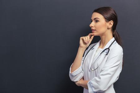 흰색 의료 가운 턱에 손을 유지하고 생각하고, 칠판에 대해 아름다운 젊은 의사의 측면보기