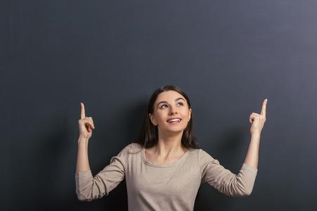 Mooie jonge vrouwelijke student glimlachen, kijken en naar boven, die zich tegen blackboard
