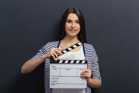 teen girl face: Beautiful young girl in casual clothes is holding a clapperboard, looking at camera and smiling, standing against blackboard
