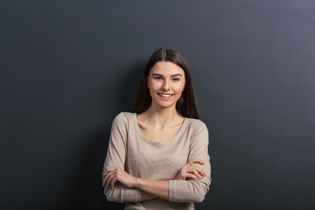 Beautiful young female student is looking at camera and smiling, standing with crossed arms against blackboard