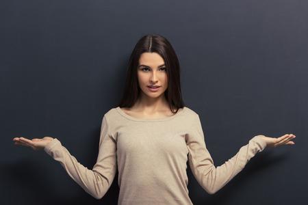 Belle jeune fille regarde la caméra et en gardant les mains propagation balance montrant, debout contre tableau noir Banque d'images