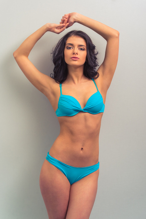 stretched: Attractive young woman in blue underwear is looking at camera and posing with stretched hands, standing against gray background Stock Photo