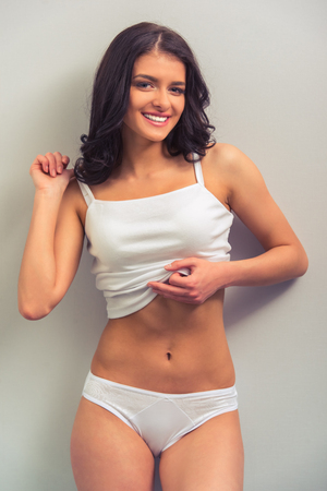 white singlet: Attractive young woman in white underwear is looking at camera, smiling and pulling her singlet, standing against gray background Stock Photo