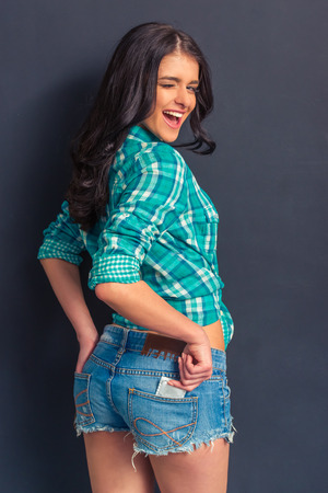 Attractive girl in jeans shorts is putting a condom into back pocket, looking at camera and winking, standing against dark background