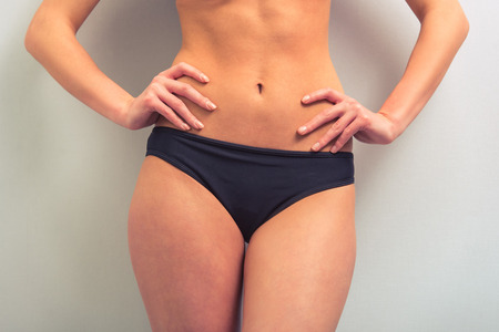akimbo: Cropped image of attractive young woman in black underwear standing akimbo against gray background
