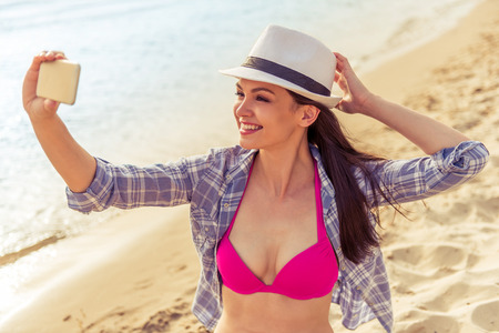 Beautiful girl in summer clothes is making selfie using a smartphone and smiling, sitting on the beach