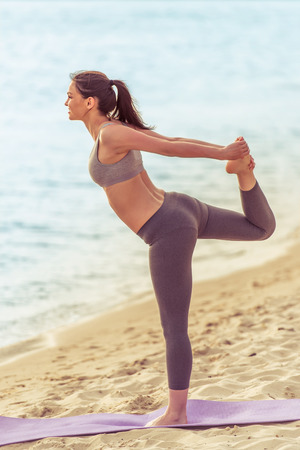 beach mat: Side view of beautiful girl in sport clothes doing yoga on mat on the beach Stock Photo