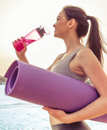beach mat: Side view of beautiful girl in sport clothes holding a yoga mat and drinking water after workout on the beach Stock Photo