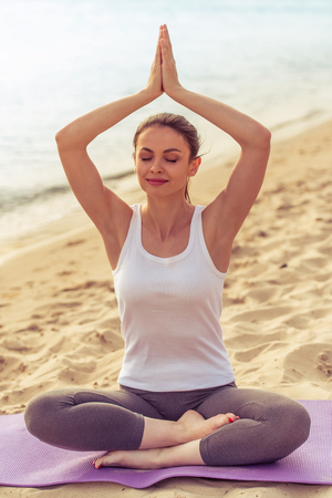 beach mat: Beautiful girl in sport clothes is meditating while sitting in lotus position on yoga mat on the beach