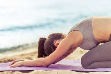 beach mat: Side view of beautiful girl in sport clothes stretching on yoga mat on the beach Stock Photo
