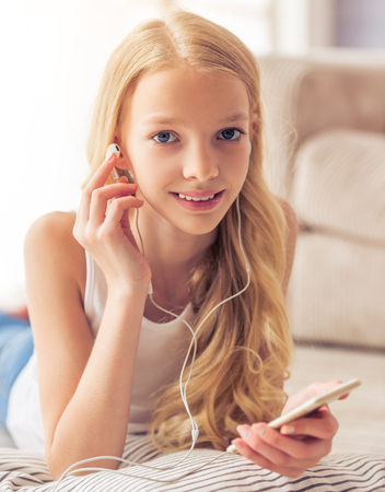 blonde teenager: Portrait of pretty blonde teenage girl in earphones listening to music using a smartphone, looking at camera and smiling while lying on cushion at home Stock Photo