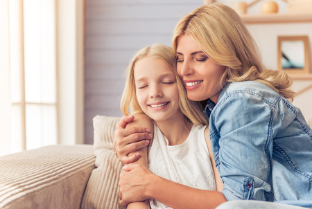 Beautiful blonde woman in jeans shirt and her teenage daughter are hugging and smiling while sitting with closed eyes on couch at home Stock Photo