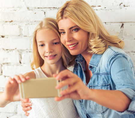 blonde teenage girl: Attractive blonde teenage girl and her mother are making selfie using a smart phone and smiling, standing against white brick wall Stock Photo
