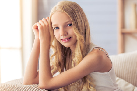 blonde teenage girl: Portrait of pretty blonde teenage girl looking at camera, smiling and leaning on her hands, sitting on sofa at home Stock Photo