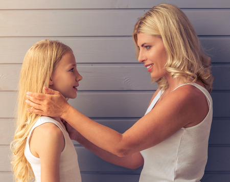 blonde teenage girl: Side view of attractive blonde teenage girl and her mother looking at each other and smiling, standing against gray wall Stock Photo