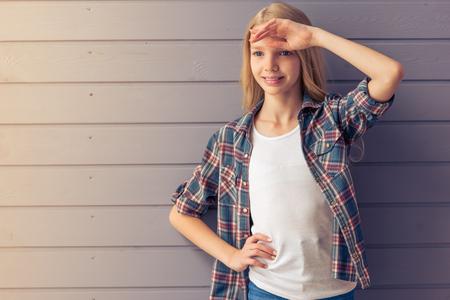 カジュアルな服装と笑顔、灰色の壁に立って、ポーズ、よそ見で魅力的な金髪の十代の少女の肖像画