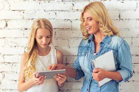 blonde teenage girl: Attractive blonde teenage girl and her mother are using tablets and smiling, standing against white brick wall Stock Photo
