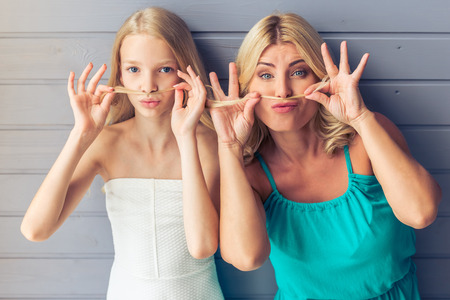 making dresses: Attractive blondes with blue eyes in dresses, teenage girl and her mother, are imitating moustache with hair, making faces and looking at camera, against gray wall