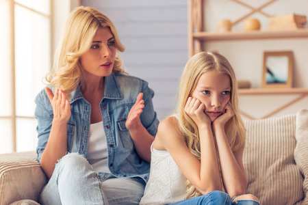 Attractive teenage girl is looking sadly away, leaning on her hands while her mother is scolding her, sitting on couch at home