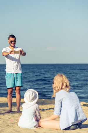 taking a wife: Handsome young man in sun glasses is taking photo of his beautiful wife and little daughter using a smartphone, standing on the sunny beach
