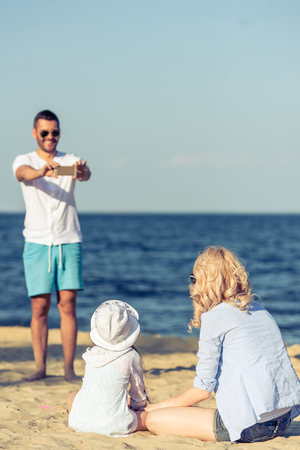 taking a wife: Handsome young man in sun glasses is taking photo of his beautiful wife and little daughter using a smartphone, standing on the sunny beach. Girls in focus Stock Photo
