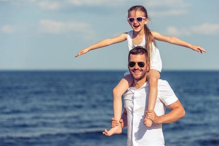 Beau jeune papa et sa petite fille mignonne dans les lunettes de soleil regardent la caméra et souriant. Fille assise sur les épaules de son père, mer ensoleillée en arrière-plan Banque d'images - 60377657